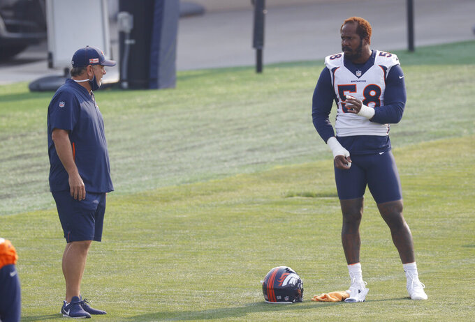 Denver Broncos linebacker Von Miller, right, chats with outside linebackers coach John Pagano during drills during an NFL football practice at the team's headquarters Monday, Aug. 24, 2020, in Englewood, Colo. (AP Photo/David Zalubowski)