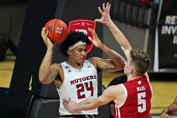 Rutgers' Ron Harper Jr., left, looks to pass the ball as Wisconsin's Tyler Wahl defends during the first half of an NCAA college basketball game Friday, Jan. 15, 2021, in Piscataway, N.J. (AP Photo/Seth Wenig)