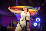 A spectator dances holding a rainbow flag at Pride Park, a venue for artistic shows ahead the Pride 2021 in Bucharest, Romania, Thursday, Aug. 12, 2021. The 20th anniversary of the abolishment of Article 200, which authorized prison sentences of up to five years for same-sex relations, was one cause for celebration during the gay pride parade and festival held in Romania's capital this month. People danced, waved rainbow flags and watched performances at Bucharest Pride 2021, an event that would have been unimaginable a generation earlier. (AP Photo/Vadim Ghirda)