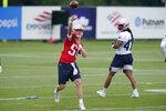 New England Patriots quarterback Mac Jones (50) passes the ball as fullback Jakob Johnson (47) looks on during an NFL football minicamp practice, Tuesday, June 15, 2021, in Foxborough, Mass. (AP Photo/Steven Senne)