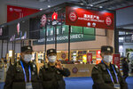 Security officers wearing face masks to protect against the coronavirus walk past a display of Australian wines and other agricultural products at the China International Import Expo (CIIE) in Shanghai, on Nov. 5, 2020. China is raising import taxes on Australian wine, stepping up pressure on Australia over disputes including its support for a probe into the origin of the coronavirus. (AP Photo/Mark Schiefelbein)