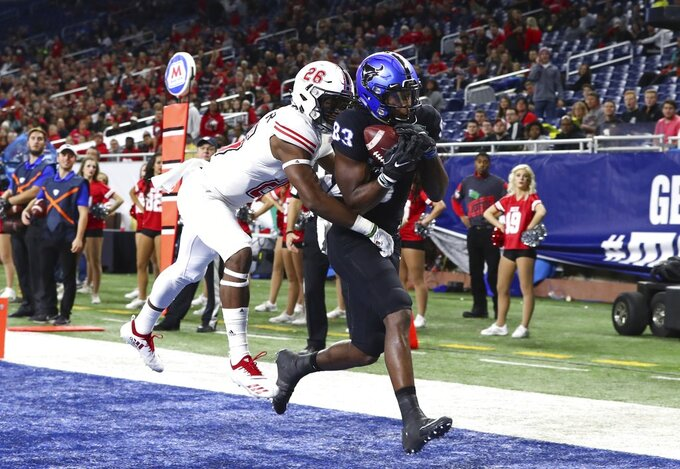 Buffalo wide receiver Anthony Johnson (83), defended by Northern Illinois cornerback Antwain Walker (26), catches a 13-yard pass for a touchdown during the first half of the Mid-American Conference championship NCAA college football game, Friday, Nov. 30, 2018, in Detroit. (AP Photo/Carlos Osorio)