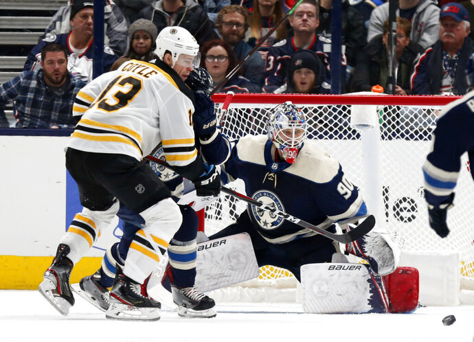 Columbus Blue Jackets goalie Elvis Merzlikins, right, of Latvia, stops a shot from Boston Bruins forward Charlie Coyle, left, during the second period an NHL hockey game in Columbus, Ohio, Tuesday, Jan. 14, 2020. (AP Photo/Paul Vernon)