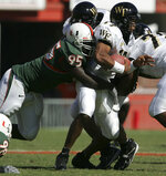FILE- In this Nov. 20, 2004, file photo, Miami's Bryan Pata sacks Wake Forest quarterback Cory Randolph in the first half of an college football game in Miami. Rashaun Jones, 35, of Lake City, a former University of Miami football player was arrested Thursday, Aug. 19, 2021, in connection with the 2006 fatal shooting of his teammate Bryan Pata. Pata, a 22-year-old, 6-foot-4, 280-pound defensive lineman, was shot several times outside of his Kendall, Fla., apartment the night of Nov. 7, 2006. (Al Diaz/Miami Herald via AP, File)