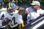 Pittsburgh Steelers running back Najee Harris (22) goes through a drill as running backs coach Steve Faulkner, right, uses a blocking dummy during an NFL football practice, Thursday, July 22, 2021, in Pittsburgh. (AP Photo/Keith Srakocic)
