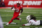 FILE - In this Dec. 19, 2020, file photo, Utah running back Ty Jordan (22) runs for a score as he eludes a tackle by Washington State linebacker Jahad Woods (13) during the second half of an NCAA college football game, in Salt Lake City.   Authorities say Jordan died at a hospital in the Dallas area after accidently shooting himself. University officials announced Ty Jordan's death Saturday, the day after he was named Pac-12's newcomer of the year. (AP Photo/Rick Bowmer, File)