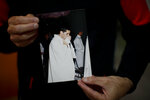 Andres Gioeni shows a photograph of his ordination ceremony to become a priest in 2000, after he got home from the bishopric where he started the process of apostasy in Buenos Aires, Argentina, Wednesday, March 17, 2021. Gioeni, who left the priesthood in 2021 and married his boyfriend in 2014, said he has decided to formally leave the church after the Vatican decreed that the Catholic Church cannot bless same-sex unions since God 'cannot bless sin.' (AP Photo/Natacha Pisarenko)