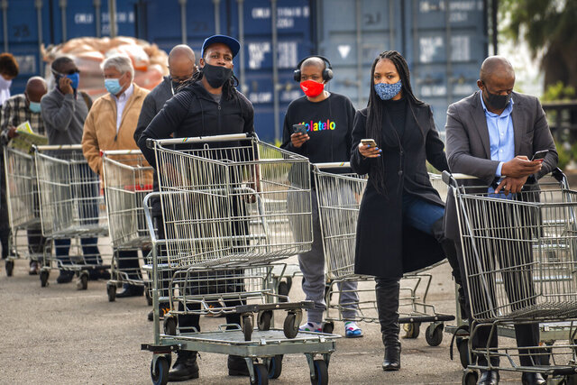 Customers lineup to enter an hyper store in Johannesburg, South Africa, Tuesday, Aug. 18, 2020.  South Africa, which had one of the world's strictest anti-coronavirus lockdowns for five months, relaxed its restrictions Tuesday to permit the sales of alcohol and cigarettes and other returns to more ordinary life in response to decreasing new cases and hospitalizations for COVID-19.(AP Photo/Jerome Delay)