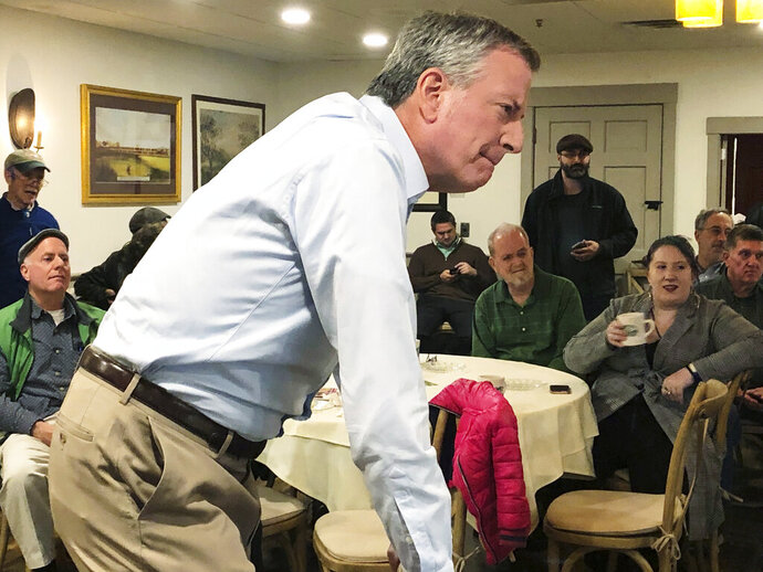 New York Mayor Bill de Blasio listens as he speaks before a group of people at a restaurant in Concord, N.H., Sunday, March 17, 2019. Blasio on Sunday criticized former President Barack Obama during the small gathering as he mulls a run for president, saying that Obama's early days in office were