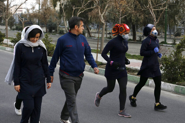 Two women jog with face masks on as others walk while enjoying their weekend afternoon at Pardisan Park in Tehran, Iran, Friday, Feb. 28, 2020. Iranians in Tehran on Friday found time to enjoy their weekend, even as authorities canceled Friday prayers and closed universities, schools and parliament over fears about the new coronavirus. (AP Photo/Vahid Salemi)