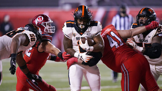 Utah defensive tackle Hauati Pututau (41) tackles Oregon State running back Calvin Tyler Jr., center, during the first half of an NCAA college football game Saturday, Dec. 5, 2020, in Salt Lake City. (AP Photo/Rick Bowmer)