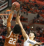 Oklahoma State guard Lindy Waters III (21) attempts to block a dunk by Texas forward Kai Jones (22) during an NCAA college basketball game in Stillwater, Okla., Wednesday, Jan. 15, 2020. (AP Photo/Brody Schmidt)