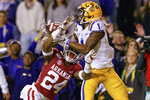 FILE - In this Nov. 23, 2019, file photo, LSU wide receiver Ja'Marr Chase (1) catches a pass for a touchdown next to Arkansas defensive back LaDarrius Bishop (24) during the first half of an NCAA college football game, in Baton Rouge, La. No. 1 LSU will meet No. 4 Georgia in the SEC Championship. (AP Photo/Matthew Hinton, File)