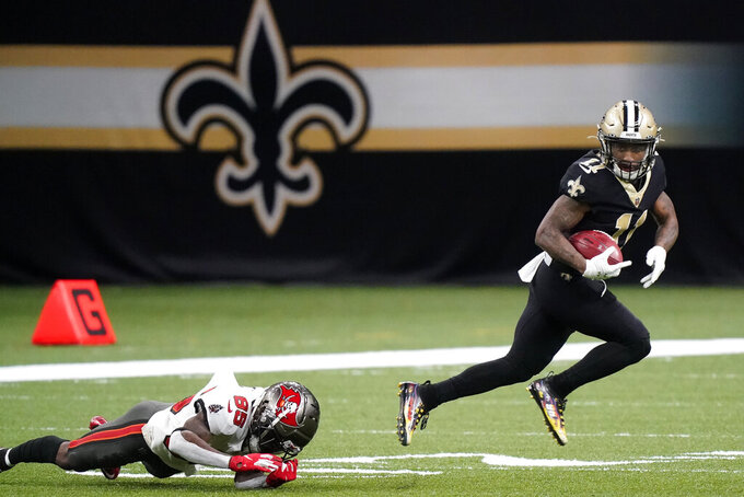 New Orleans Saints' Deonte Harris (11) returns a punt past Tampa Bay Buccaneers' Jaydon Mickens (85) during the first half of an NFL divisional round playoff football game, Sunday, Jan. 17, 2021, in New Orleans. (AP Photo/Brynn Anderson)