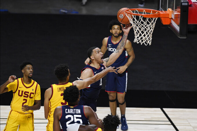 Connecticut's Tyrese Martin goes up for a basket during the first half of the team's NCAA college basketball game against Southern California, Thursday, Dec. 3, 2020, in Uncasville, Conn. (AP Photo/Jessica Hill)