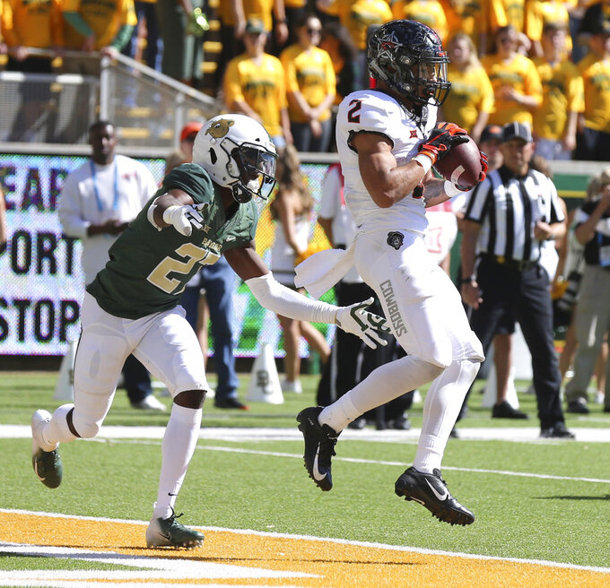 Oklahoma State's wide receiver Tylan Wallace, right, scores ahead of Baylor's Kalon Barnes, left, in the first second of an NCAA college football game, Saturday, Nov. 3, 2018, in Waco, Texas. (Rod Aydelotte/Waco Tribune Herald, via AP)/Waco Tribune-Herald via AP)