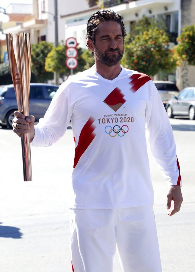 "US actor Gerard Butler poses as a torchbearer during the Olympic torch relay of the 2020 Tokyo Olympic Games in the southern Greek town of Sparta, Friday, March 13, 2020. Greece's Olympic committee says it is suspending the rest of its torch relay for the Olympic flame due to the ""unexpectedly large crowd"" that gathered to watch despite repeated requests for the public to stay away to prevent the spread of the new coronavirus. (AP Photo)"