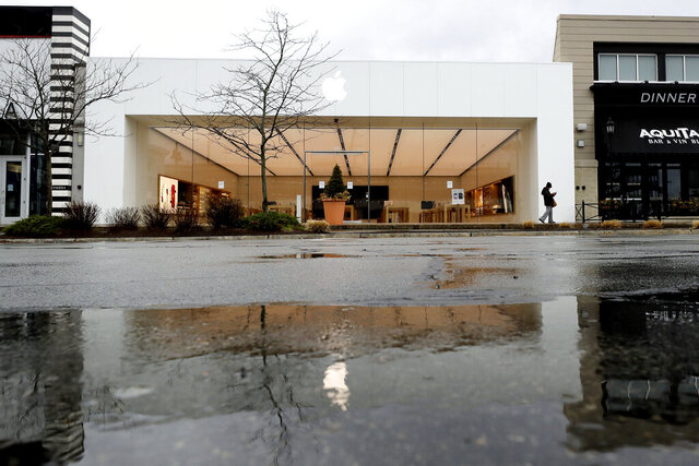 A person walks past a closed Apple Store, Thursday, April 9, 2020, in Dedham, Mass. Many people are working from home and many business have indefinitely closed out of concern about the coronavirus. (AP Photo/Steven Senne)