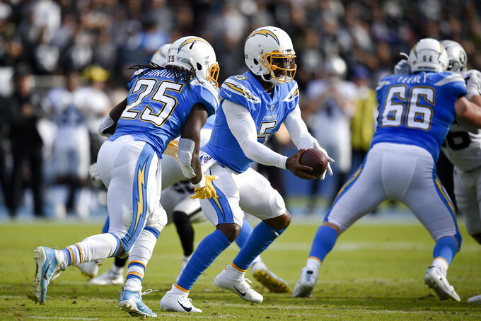 FILE - In this Dec. 22, 2019, file photo, Los Angeles Chargers quarterback Tyrod Taylor, center, prepares to hand off the ball to Melvin Gordon III during the first half of an NFL football game against the Oakland Raiders in Carson, Calif. Taylor has the inside track to be the Chargers' quarterback, but coach Anthony Lynn said the team is still assessing all of their options.(AP Photo/Kelvin Kuo, File)