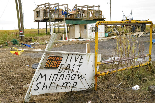 FILE - In this Oct. 30, 2020 file photo, a bait shop and neighboring building is seen damaged by Hurricane Zeta in Golden Meadow, La.  Hurricane Zeta left much of lower Terrebonne and lower Lafourche parishes in shambles when it made landfall on Oct. 28.  (AP Photo/Matthew Hinton, File)