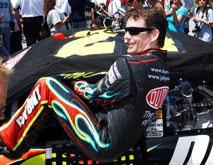 FILE - In this April 25, 2010, file photo, Jeff Gordon climbing into his car as he prepares to start the NASCAR Sprint Cup Series Aaron's 499 auto race at Talladega Superspeedway in Talladega, Ala. Gordon headlines the 10th class of the NASCAR Hall of Fame for his storied career on and off the track. He'll be inducted on Friday night, Feb. 1,2019, along with NASCAR team owners Roger Penske and Jack Roush.  (AP Photo/Rainier Ehrhardt, File)