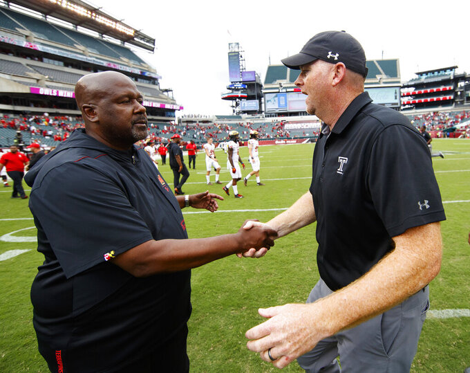 Maryland head coach Michael Locksley, left, shakes hands with Temple head coach Rod Care, right, following an NCAA college football, Saturday, Sept. 14, 2019, in Philadelphia. Temple won 20-17. (AP Photo/Chris Szagola)