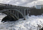 In this Jan. 11, 2020 photo heavy surf surrounds the legs of a bridge as an extreme high tide rolls into the harbor in Depoe Bay, Ore. during a so-called
