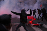 Youths throw items at police forces during a demonstration in Paris, Thursday, Dec. 5, 2019. Small groups of protesters are smashing store windows, setting fires and hurling flares in eastern Paris amid mass strikes over the government's retirement reform. (AP Photo/Thibault Camus)