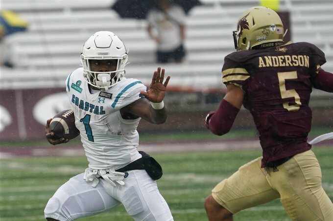 Coastal Carolina's CJ Marable (1) runs for a long gain as Texas State's Kevin Anderson (5) pursues during the first half of an NCAA college football game in Austin, Texas, Saturday, Nov. 28, 2020. (AP Photo/Chuck Burton)