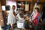 Members of an election commission come to an elderly family to help them attend a voting at their house in Starozolotovsky village, 160 km (100 miles) north of Rostov-on-Don during the Parliamentary elections , Russia, Saturday, Sept. 18, 2021. Sunday is the last of three days voting for a new parliament, but there seems to be no expectation that United Russia, the party devoted to President Vladimir Putin, will lose its dominance in the State Duma. (AP Photo)