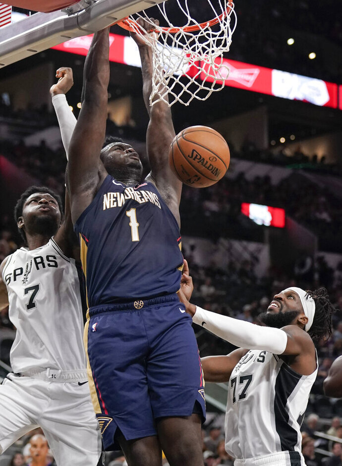 New Orleans Pelicans' Zion Williamson (1) dunks as he is defended by San Antonio Spurs' Chimezie Metu (7) and DeMarre Carroll during the first half of an NBA preseason basketball game, Sunday, Oct. 13, 2019, in San Antonio. (AP Photo/Darren Abate)