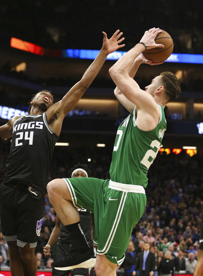 Boston Celtics forward Gordon Hayward, right, goes up for the go-ahead shot against Sacramento Kings guard Buddy Hield in the closing moments of the Celtics' 111-109 win in an NBA basketball game Wednesday, March 6, 2019, in Sacramento, Calif. (AP Photo/Rich Pedroncelli)