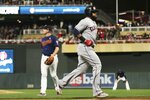 Cleveland Indians' Yasiel Puig, right, jogs home on a wild pitch by Minnesota Twins pitcher Tyler Duffey, left, with a go-ahead run in the sixth inning of a baseball game Saturday, Sept 7, 2019, in Minneapolis. (AP Photo/Jim Mone)