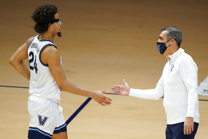 Villanova's Jeremiah Robinson-Earl, left, and head coach Jay Wright celebrate during the second half of an NCAA college basketball game against Saint Joseph's, Saturday, Dec. 19, 2020, in Villanova, Pa. (AP Photo/Matt Slocum)