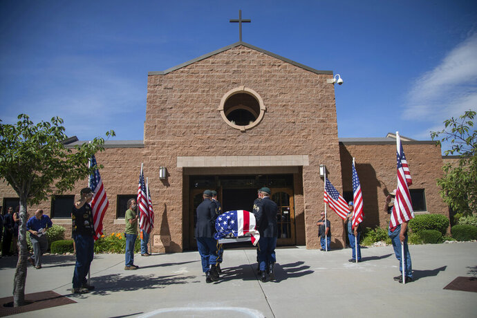 Military personnel carry the remains of Army Sgt. 1st Class Elliott Robbins into St. James Catholic Church in Ogden, Utah on Thursday, July 18, 2019. Robbins died in a non-combat incident on June 30 while serving in Afghanistan.  (Ben Dorger/Standard-Examiner via AP)