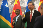 Solomon Islands Foreign Minister Jeremiah Manele, left, and Chinese Foreign Minister Wang Yi hold glasses for a toast during a ceremony to mark the establishment of diplomatic relations between the Solomon Islands and China at the Diaoyutai State Guesthouse in Beijing, Saturday, Sept. 21, 2019. (AP Photo/Mark Schiefelbein, Pool)
