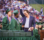 Longview Lobos Kamden Perry, left, and Jephaniah Lister present actor and 1988 Longview High School graduate Matthew McConaughey with an autographed football and his own state championship ring at the school's graduation ceremony in Longview, Texas, on Friday, May 17, 2019. McConaughey has finally received his high school diploma, more than 30 years after graduating. (Les Hassell/The News-Journal via AP)