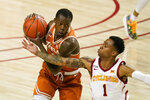 Texas guard Andrew Jones catches a pass over Iowa State guard Tyler Harris, right, during the first half of an NCAA college basketball game, Tuesday, March 2, 2021, in Ames, Iowa. (AP Photo/Charlie Neibergall)