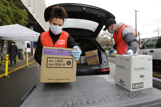 Volunteers Keshia Link, left, and Dan Peterson unload boxes of donated gloves and alcohol wipes from a car at a drive-up donation site for medical supplies at the University of Washington to help fight the coronavirus outbreak Tuesday, March 24, 2020, in Seattle. (AP Photo/Elaine Thompson)