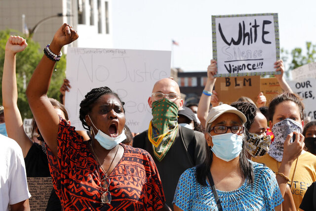 Protesters chant as they march in the street way from the City Justice Center Monday, June 1, 2020, in St. Louis. Protesters gathered to speak out against the death of George Floyd who died after being restrained by Minneapolis police officers on May 25. (AP Photo/Jeff Roberson)