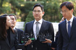 Samsung Electronics Vice Chairman Lee Jae-yong, center, arrives at the Seoul High Court in Seoul, South Korea, Friday, Oct. 25, 2019. Billionaire Samsung scion Lee appeared in court for a retrial on corruption charges that partially fueled an explosive 2016 scandal that spurred massive protests and sent South Korea's then-president to prison. (AP Photo/Ahn Young-joon)
