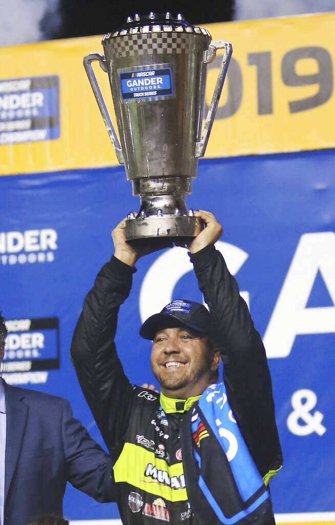 Matt Crafton celebrates in Victory Lane after winning the NASCAR Truck Series auto racing season championship Friday, Nov. 15, 2019, at Homestead-Miami Speedway in Homestead, Fla. (AP Photo/David Graham)
