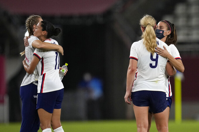 United States players embrace after being defeated 1-0 by Canada during a women's semifinal soccer match at the 2020 Summer Olympics, Monday, Aug. 2, 2021, in Kashima, Japan. (AP Photo/Andre Penner)