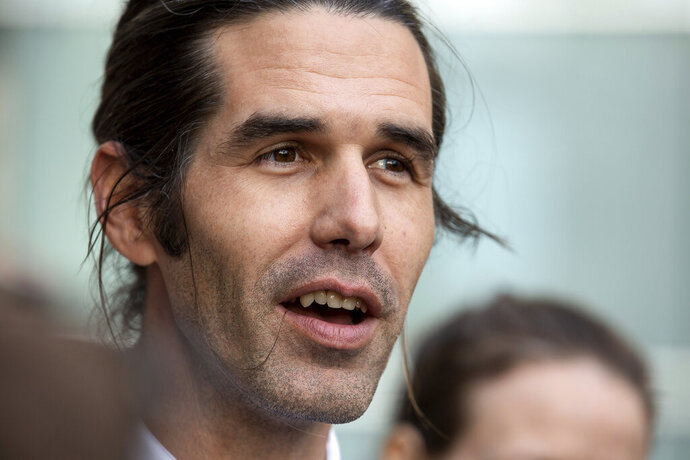 Border aid volunteer Scott Warren talks with media and supporters outside the Federal Courthouse, Wednesday, Nov. 20, 2019 in Tucson, Ariz. Warren was acquitted Wednesday on charges he illegally harbored two Central American immigrants at a camp in southern Arizona operated by a humanitarian group. (Josh Galemore/Arizona Daily Star via AP)