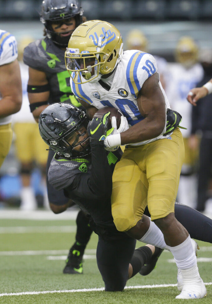 Oregon's Nick Pickett tackles UCLA's Demetric Felton during the third quarter of an NCAA college football game Saturday, Nov. 21, 2020, in Eugene, Ore. (AP Photo/Chris Pietsch)