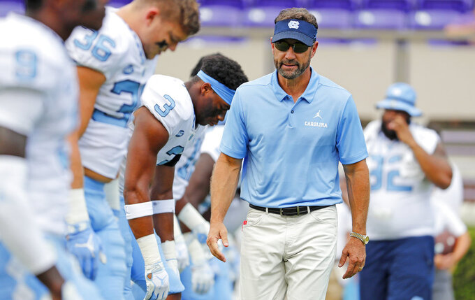 FILE - In this Sept. 8, 2018, file photo, North Carolina coach Larry Fedora, right, walks next to players warming up for an NCAA college football game against East Carolina in Greenville, N.C. Fedora's Tar Heels host Virginia Tech on Saturday. (AP Photo/Karl B DeBlaker, File)