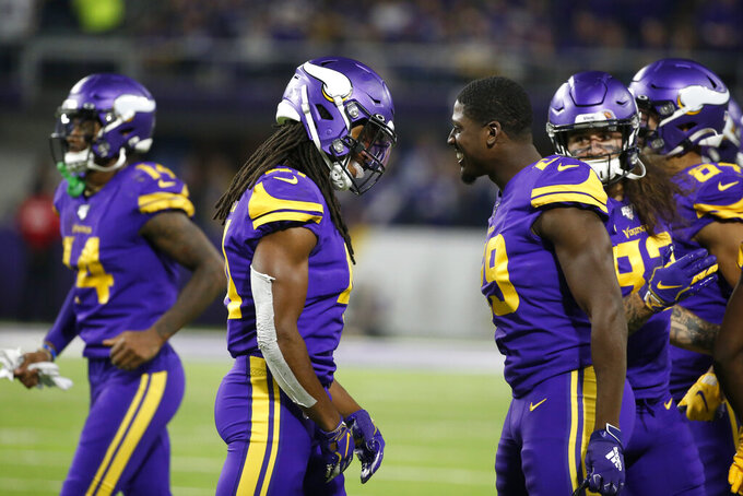 Minnesota Vikings defensive back Anthony Harris, left, celebrates with teammate Xavier Rhodes, right, after intercepting a pass during the second half of an NFL football game against the Washington Redskins, Thursday, Oct. 24, 2019, in Minneapolis. (AP Photo/Bruce Kluckhohn)