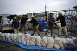 Workers stack sandbags at a construction site in preparation for Typhoon Hagibis on Enoshima Island, Kamakura, west of Tokyo, Friday, Oct. 11, 2019. A typhoon was forecast to bring 2 feet of rain and damaging winds to the Tokyo area and central Japan's Pacific coast this weekend, and the government warned people Friday to stockpile and leave high-risk places before it's too dangerous. (AP Photo/Jae C. Hong)