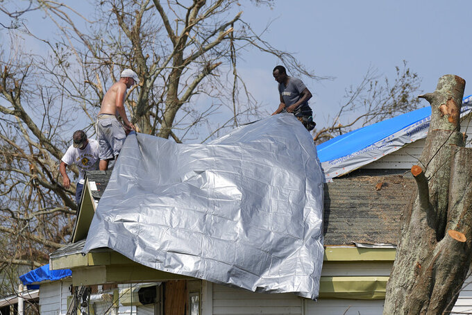Gary Johnston, left, Grant Boughamer, center, and Jose Garcia, right, place a tarp on a roof damaged by Hurricane Ida, Thursday, Sept. 2, 2021, in Golden Meadow, La. (AP Photo/David J. Phillip)