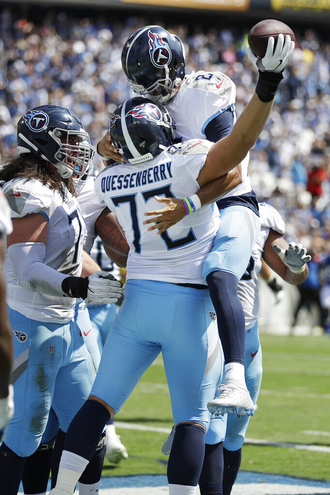 Tennessee Titans' David Quessenberry (72) celebrates with quarterback Marcus Mariota (8) after catching a touchdown pass from Mariota against the Indianapolis Colts in the first half of an NFL football game Sunday, Sept. 15, 2019, in Nashville, Tenn. (AP Photo/James Kenney)